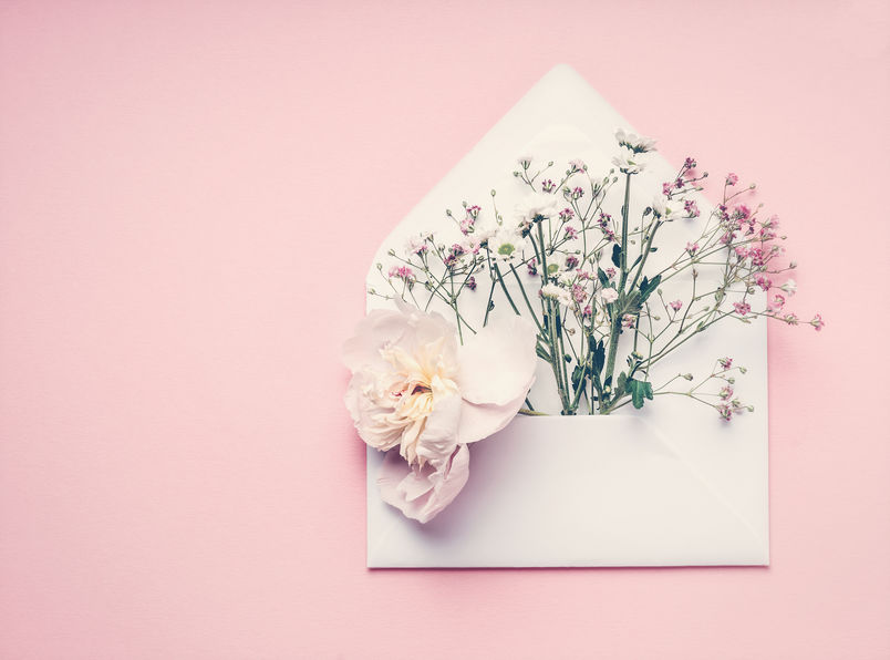 Opened envelop with flowers arrangement on pastel pink background, top view, copy space. Creative greeting, Invitation and holiday concept
